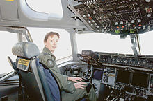 Colour photo of a woman wearing a green flight suit sitting inside an aircraft cockpit