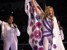 A blond woman wearing a white and purple leotard, with a cape around her, sings in to a microphone. She is flanked by two similarly dressed women.