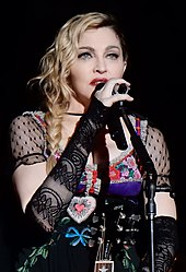 Madonna singing while holding a microphone with her right hand.