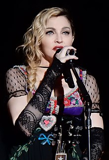 A closeup photo of Madonna with shoulder-length wavy blonde hair, heavy makeup and a colorful, low-cut blouse
