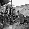 Man gooit kolen op het vuur van de distilleerketel, Bestanddeelnr 252-9468.jpg