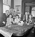 Mannen en vrouwen poserend achter een tafel met een drankje, Bestanddeelnr 255-8518.jpg
