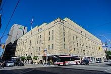 """Una vista esterna di un edificio.  L'edificio ha un cartello che dice """"Maple Leaf Gardens"""" sulla parte anteriore."""