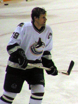 Markus Näslund -  alt = An ice hockey player skating on the ice. He wears a white jersey with black trim and is helmetless. He looks forward and holds his stick horizontally across his torso in a relaxed fashion.
