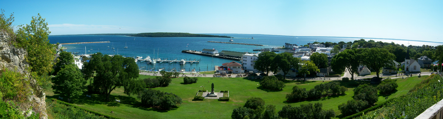 A panoramic view of a park. To the left is a rocky cliff. A wide green space, named Marquette Park, can be seen in the foreground. Ships are docked in a harbor in the background, and another island is visible in the distance.