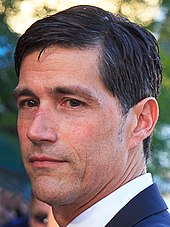 Matthew Fox behind the microphone at a convention.
