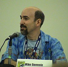 "A bald man with a beard speaks into a microphone. A plaque with the Comic-Con logo on the table reads ""Mike Stemmle""."