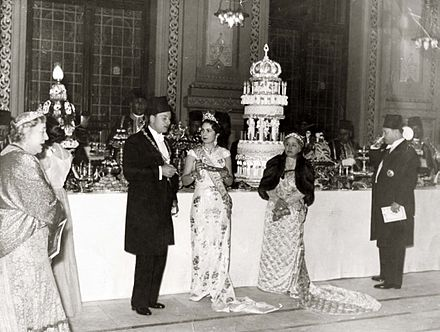 A banquet organised on the occasion of the wedding of King Farouk I and Queen Farida of Egypt. The persons appearing in the photograph are (from left to right): Princess Nimet Mouhtar (1876-1945), Farouk's paternal aunt; King Farouk I (1920-1965), the groom; Queen Farida (1921-1988), the bride; Sultana Melek (1869-1956), widow of Hussein Kamel, Farouk's paternal uncle; Prince Muhammad Ali Ibrahim (1900-1977), Farouk's 2nd cousin once removed. ModernEgypt, Farouk & Farida Marriage, DHP13655-20-9 01.jpg