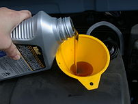 Using a funnel to refill the motor oil in an a...
