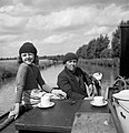 Mrs Gribbis and her daughter Valerie enjoy a lunchtime cup of tea as they steer the 'butty', being towed by Mr Gribbis' narrowboat on the Grand Union Canal during 1944. D21788.jpg
