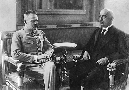 At Belweder Palace, Chief of State Pilsudski (left) transferred his powers to President-elect Gabriel Narutowicz (right). Two days later, the President was assassinated. Narutowicz Pilsudski.jpg