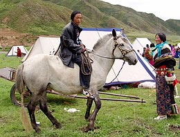 A man riding a horse talking with a woman in front of a tent. The man wears contemporary clothes while the woman seem wearing more traditional garments.
