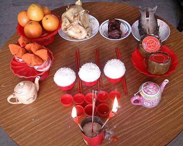 Prayers and simple offerings to the Chinese gods during Chinese New Year. Clockwise from upper left: tangerines, chicken, pork, fish, nian gao, tea, rice and fa gao. 新春祭祀眾神明 (30 January 2014)