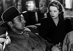 Black-and-white image of a man and a woman sitting side by side on a couch, viewed at an angle. The man, in profile in the left foreground, stares off to the right of frame, he wears a trenchcoat, and his face is shadowed by a fedora. He holds a cigarette in his left hand, the woman, to the right and rear, stares at him. She wears a dark dress and lipstick of a deeply saturated hue.