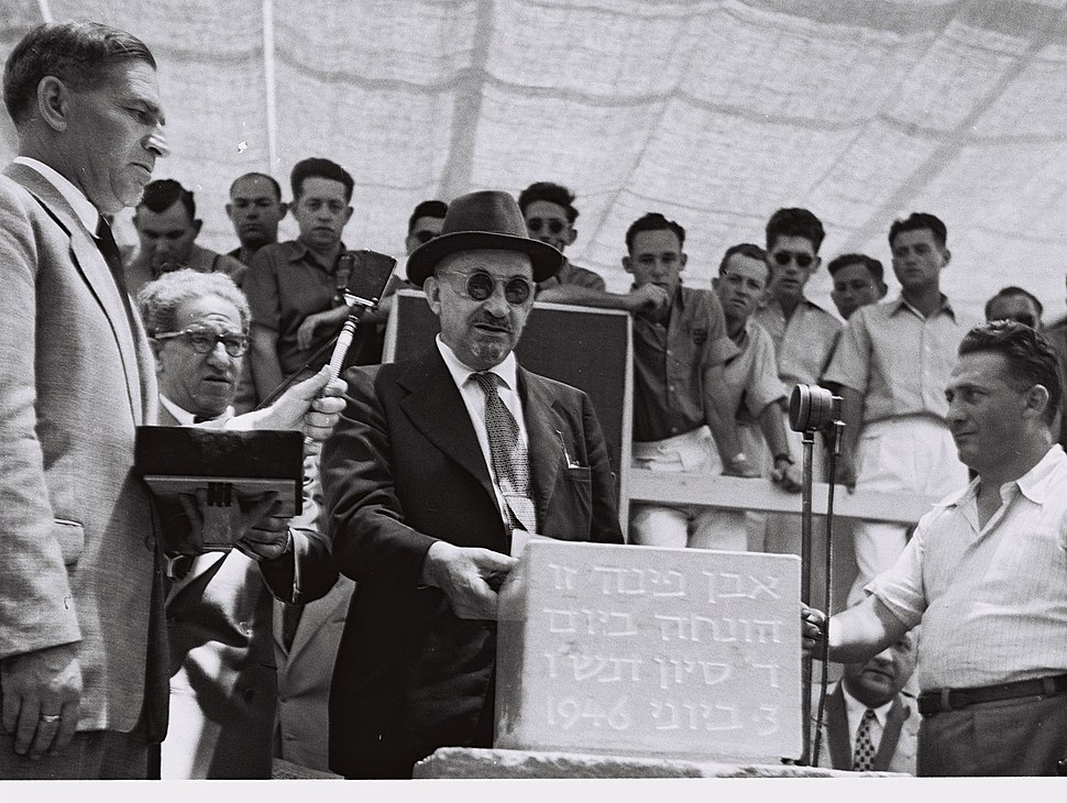 PROF. CHAIM WEIZMANN WITH HIS SECRETARY MEIR WEISSGAL STANDING BEHIND HIM (L) TOUCHING THE EMBOSSED CORNERSTONE FOR THE WEIZMANN INSTITUTE IN REHOVOT.D671-030