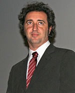 Photograph of an Italian male wearing a black coat, a white collared shirt, and a red tie with silver stripes.
