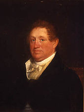 A red-haired man wearing a black jacket and white high-collared shirt