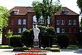 Pomnik patrona Bartoszyc - Św. Brunona, na tle budynku Liceum Ogólnokształcącego im. St. Żeromskiego w Bartoszycach. - panoramio.jpg