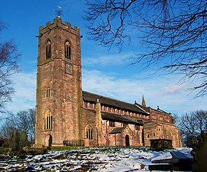 A red sandstone church with a tall battlemented west tower