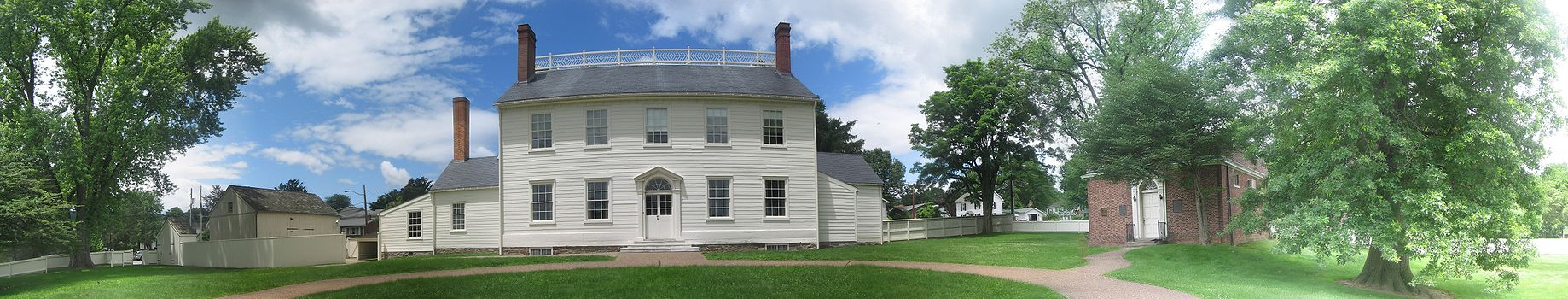A two-story white house with one-storey wings on each side, many windows, a central door, three chimneys, and a balustrade. A white latrine and barn are on the left, and a small red brick building with a white door is on the right. A white wooden fence encloses the whole yard, which has several large trees. The sky is blue with white clouds.