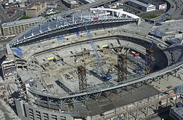 A stadium under construction with two cranes positioned where the field will eventually be installed. The terraced seating sections rise above the partially complete concourse levels, and half of the roof is in place.