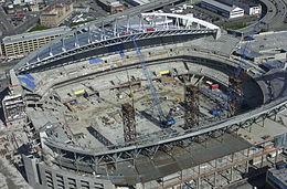 Uno stadio in costruzione con due gru posizionate in cui sarà eventualmente installata sul campo.  Le sezioni sedere schiera salgono al di sopra dei livelli concourse parzialmente completi, e la metà del tetto è a posto.