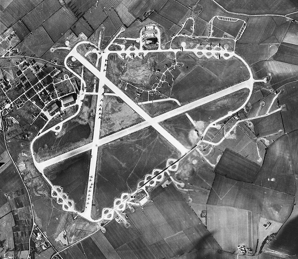 Aerial photograph of North Luffenham airfield, 2 March 1944. The technical site with two T2 hangars are at the left (west). There are three more T2 hangars and the bomb dump north of the perimeter track. A large number of aircraft are parked on the north/south crosswind runway and on the hardstand loops around the perimeter track