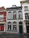 foto van Huis met gepleisterde lijstgevel, vensters met afgeronde bovenhoeken en kuiven van stuc schilddak