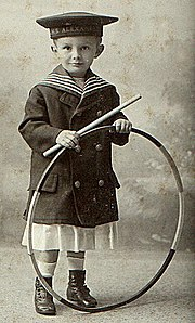 A boy with a hoop. Hoops have long been a popular toy across a variety of cultures.