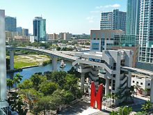 "A small metro train on an elevated rail line crosses over a wide river, surrounded by high-rise buildings. An elevated metro station with a large ""M"" sculpture is in the foreground."