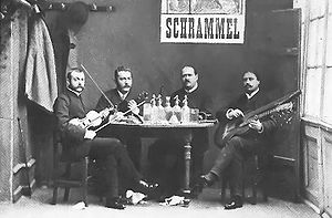 "Four musicians with instruments are seated at a table as they face the camera. The lower section of a poster appears on the back wall, displaying the name ""Schrammel."""