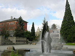 Centennial Fountain, designed by George Tsutakawa. From left to right in the background are Garrand Hall (School of Nursing), the Administration Building, and Piggot Hall (Albers School of Business).