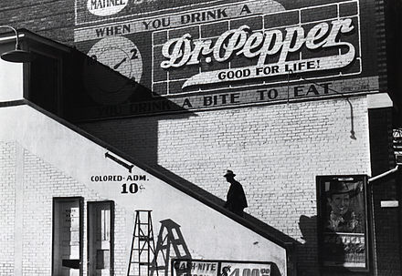 "A black man goes into the ""colored"" entrance of a movie theater in Belzoni, Mississippi, 1939 (Wikipedia, ""Racial segregation in the United States"")."