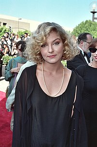 A blonde woman in a black dress looking at the camera