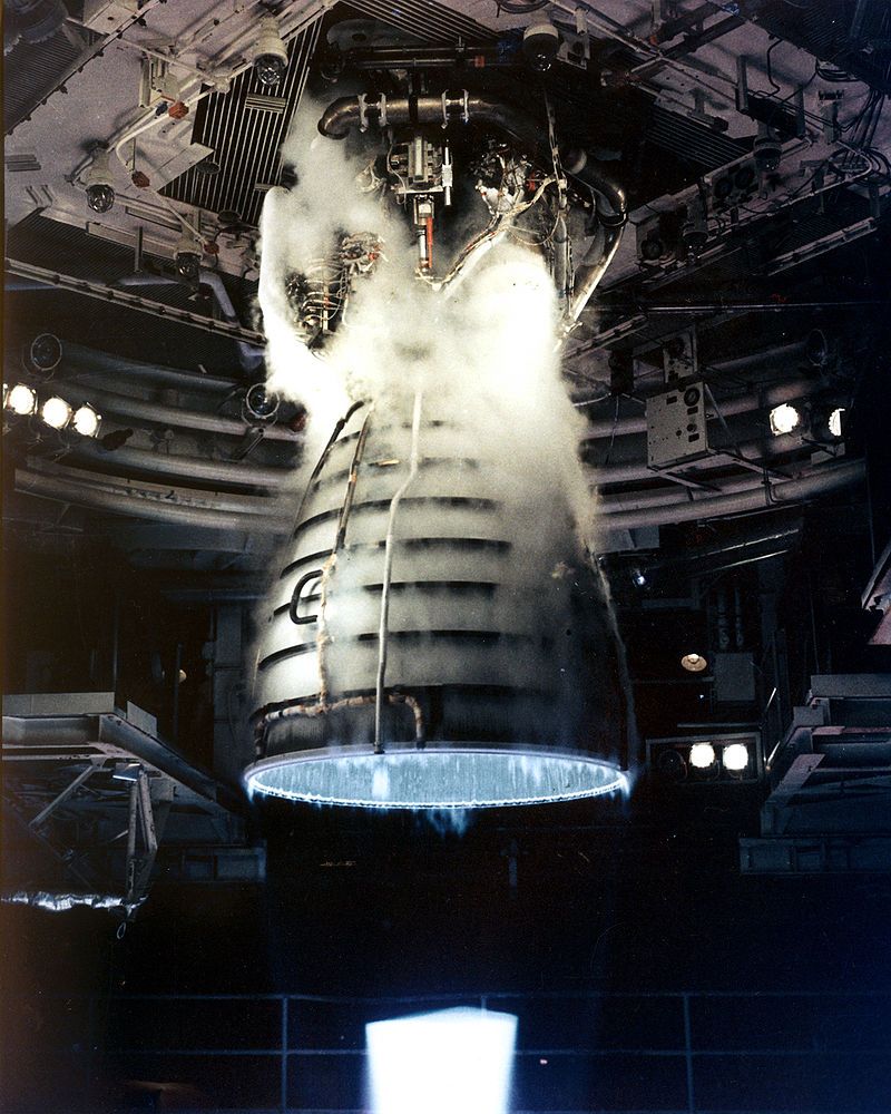 A rocket engine firing. A blue flame is projecting from a bell-shaped nozzle with several pipes wrapped around it. The top of the nozzle is attached to a complex collection of plumbing, with the whole assembly covered in steam and hanging from a ceiling-mounted attachment point. Various pieces of transient hardware are visible in the background.