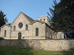 The west end of a stone church with three gable ends, a circular window and a doorway and more windows with round heads