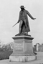 A statue of a man wearing cape and hat, and holding a sword standing to the left
