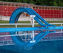 Two blue body slides, similar to playground slides, on the far side of a swimming pool