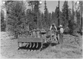 The Biles-Coleman slash piling tractor with blade raised. Over the top of the tractor there can be seen a slash pile... - NARA - 298672.tif