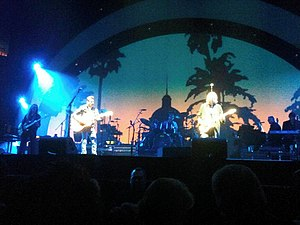 "Hotel California (Eagles album) - Eagles performing ""Hotel California"" in 2010 with the image from the album cover in the background"