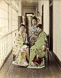 1885 hand-coloured albumen silver print by Farsari of three Maiko posing on an engawa