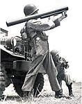 Trooper stands with Redeye missile laucnher, back against the vehicle 1960.jpg