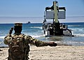 U.S. Navy Seaman Jarron Jackson, assigned to Beachmaster Unit 1, directs a rough terrain container handler as it unloads supplies from an Improved Navy Lighterage System during a maritime prepositioning force 130613-N-OP638-048.jpg