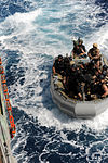 U.S. Sailors and Marines with the visit, board, search and seizure team, currently assigned to the guided missile cruiser USS San Jacinto (CG 56), climb onboard from a rigid hull inflatable boat, after 100524-N-EF447-244.jpg