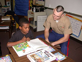 Reading comprehension - A U.S. Marine helps a student with reading comprehension as part of a Partnership in Education program sponsored by Park Street Elementary School and Navy/Marine Corps Reserve Center Atlanta. The program is a community out-reach program for sailors and Marines to visit the school and help students with class work.