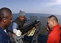 US Navy 050322-N-2198V-005 Aviation Support Equipment Technician Airman Keith Broddy, left, Torpedoman 3rd Class Samuel Irwin, center, and Aviation Ordnanceman 2nd Class Mark Baleto dismantle a .50-caliber machine gun mount.jpg