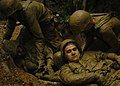 US Navy 050817-N-1261P-214 U.S. Navy Information Systems Technician 3rd Class Gero A. Spearman acts as an injured Seabee while the remaining members of his squad pulls him through mud-filled trenches as part of an obstacle cour.jpg