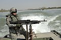 US Navy 060321-N-8252B-025 Master Sgt. Nardo Dedicatoria keeps watch of the Euphrates River shores. Company E, 1st Battalion, 67th Armored Regiment performs a reconnaissance mission of the Musayyib Bridge.jpg