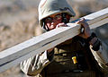 US Navy 071228-N-0553R-003 Builder 1st Class Mark Bush assigned to Naval Mobile Construction Battalion (NMCB) 1, carries lumber around a project site.jpg