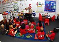US Navy 100227-N-0995C-010 A Sailor reads to a class of kindergarten students at Iroquois Point Elementary School.jpg